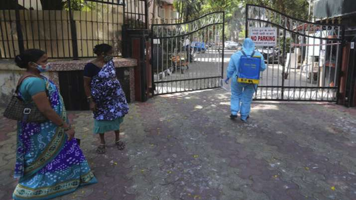 A civic worker sanitizes the gates of a residential
