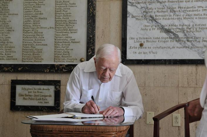 Former US President Jimmy Carter writes in the guest book at the end of his visit to the Cuban Jewish Community centre in Havana, on March 28, 2011.