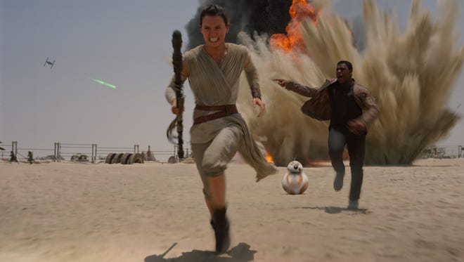 "Rey (Daisy Ridley, left), BB-8 and Finn (John Boyega) hightail it in ""Star Wars: The Force Awakens."""
