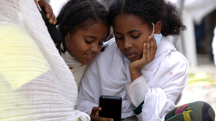 Two girls looking at out a mobile phone in Addis Ababa, Ethiopia - Friday 30 April 2021
