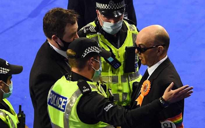 Police and officials speak to Derek Jackson, before he is ejected from the premises - AFP