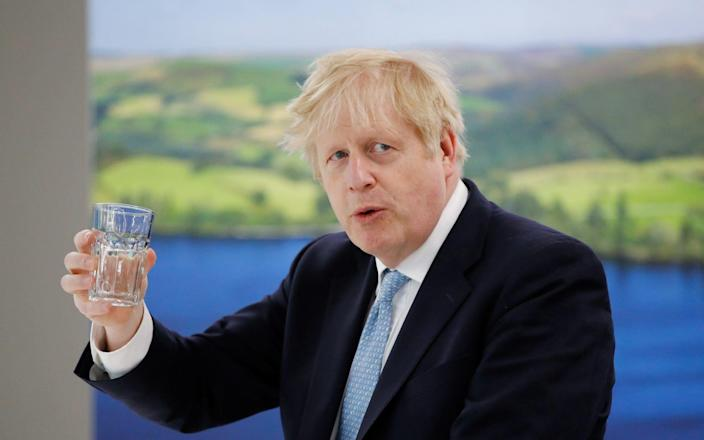 Boris Johnson holds a glass during a visit to Severn Trent Academy in Coventry, - Reuters