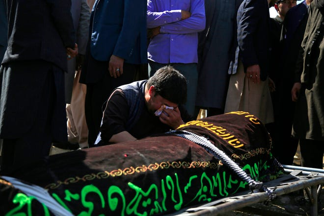 A man cries over the body of a victim of deadly bombings on Saturday near a school, at a cemetery west of Kabul, Afghanistan, on May 9, 2021. The Interior Ministry said Sunday the death toll in the horrific bombing at the entrance to a girls' school in the Afghan capital has soared to some 50 people, many of them pupils between 11 and 15 years old, and the number of wounded in Saturday's attack has also climbed to more than 100.