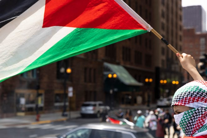 A supporter holds up a flag during a rally and march in support of Palestinians in Chicago, May 16, 2021.