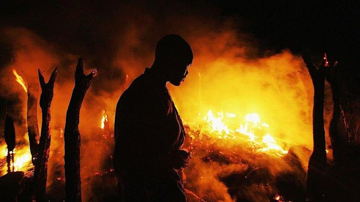 A Sudanese rebel fighter from the Justice and Equality Movement (JEM) sombrely watches the abandoned village of Chero Kasi burn less than an hour after Janjaweed militiamen set it ablaze in the violence plagued Darfur region September 7, 2004.