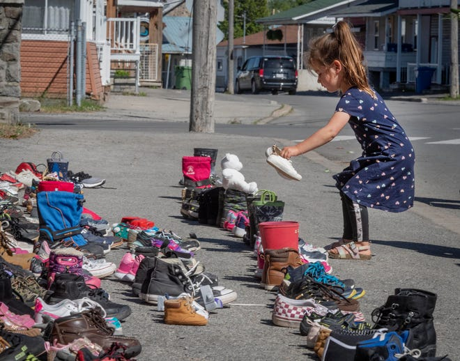A four-year-old girl places a pair of her own shoes in front of the St. Francis Xavier Church St. Francis Xavier Church in Kahnawake, Quebec on Saturday, May 29, 2021, as a memorial to the 215 children whose remains have been found buried at the site of a former residential school in Kamloops.