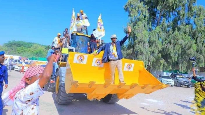 Barkhad Jama Hersi Batun and other members of the Waddani party on the campaign trail on a bulldozer