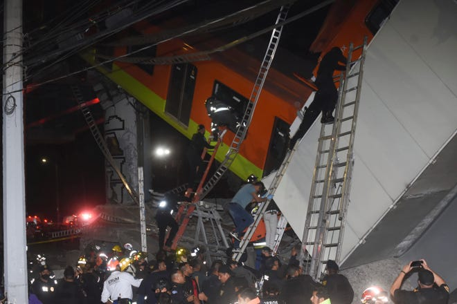 Mexico City firefights and rescue personnel are pictured recovering victims after an overpass in Mexico City's metro collapsed onto a road Monday night.
