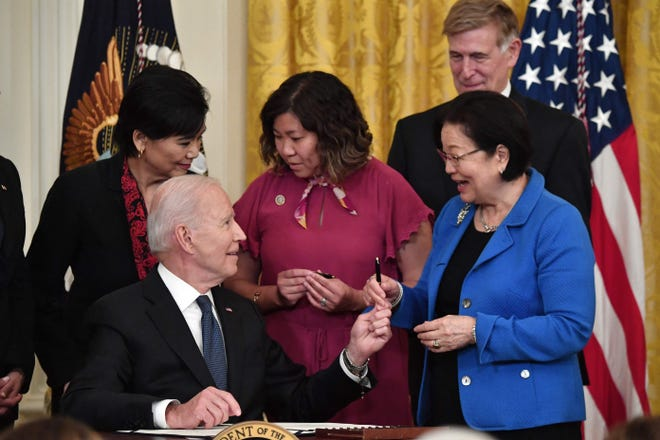 President Joe Biden hands over a pen to Senator Mazie Hirono (D-HI) after signing the Covid-19 Hate Crimes Act in the East Room of the White House.