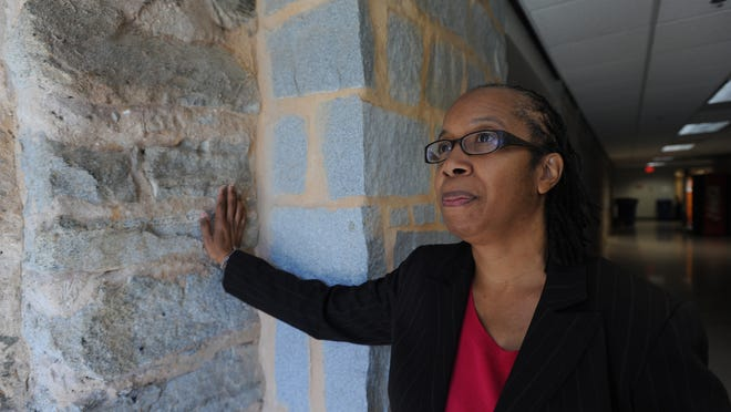 Clemson University Professor Rhondda Thomas touches stone work inside Hardin Hall. The stones came from slave cabins on John C. Calhoun's plantation, which now makes up the Clemson campus.