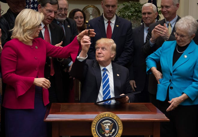In friendlier days, President Donald Trump gives a pen to Rep. Liz Cheney, R-Wyo., after signing legislation at the White House on March 27, 2017.
