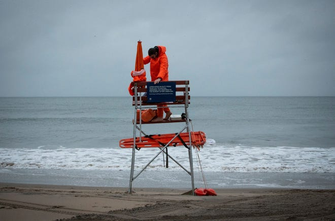 A lifeguard sets up his equipment as rain falls during Memorial Day weekend in Coney Island in New York on May 30, 2021.