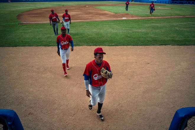 Cuban baseball player Cesar Prieto, front, walks on the field during a break from a training session at the Estadio Latinoamericano in Havana, Cuba.