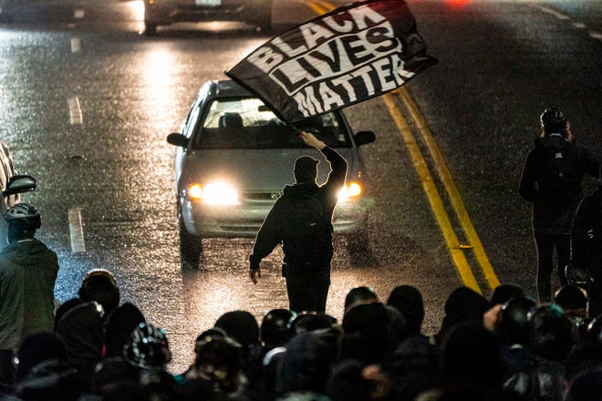 A protester waves a Black Lives Matter flag during racial justice protests on Nov. 3, 2020. in Seattle.