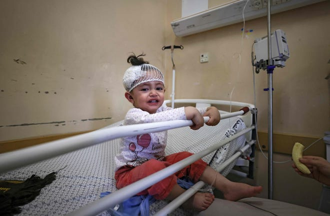 A Palestinian girl who was wounded in Israeli air strikes on the Gaza Strip, receives treatment at Al-Shifa Hospital in the Palestinian enclave on May 16, 2021.