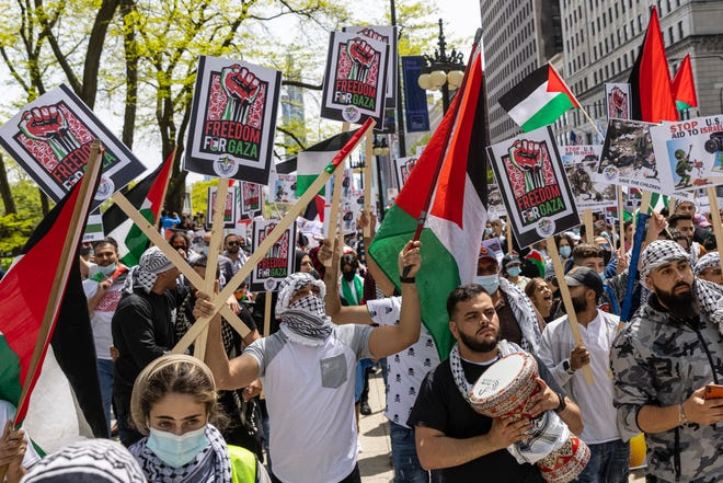 Supporters hold up flags and posters during a rally and march in support of Palestinians in Chicago in response to ongoing fighting between Israelis and Palestinians in the Middle East, on Sunday, May 16, 2021. (Anthony Vazquez/Chicago Sun-Times via AP)  ORG XMIT: ILCHS222