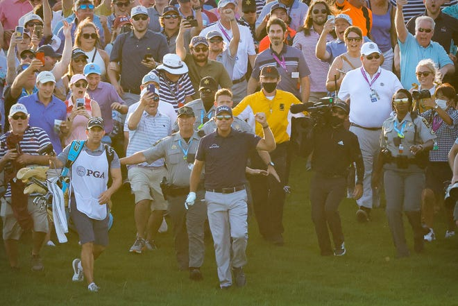 Phil Mickelson and caddie Tim Mickelson walk to the 18th green during the final round of the PGA Championship.