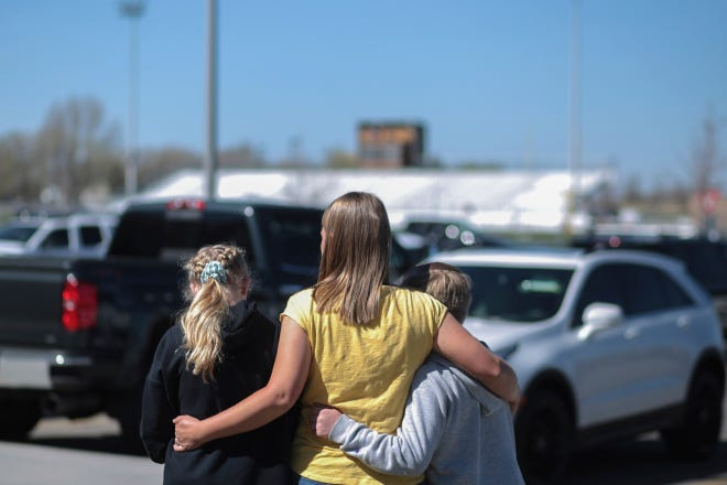 People embrace outside after a shooting at Rigby Middle School in Rigby, Idaho on Thursday, May 6, 2021. Authorities say a shooting at the eastern Idaho middle school has injured two students and a custodian, and a female student has been taken into custody.
