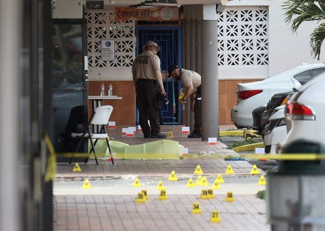 Miami-Dade police investigate near shell case evidence markers on the ground where a mass shooting took place outside of a banquet hall on May 30, 2021 in Hialeah, Florida. Police say that two people died, and an estimated 20 to 25 people are injured after the shooting at the banquet hall rented out for a concert.