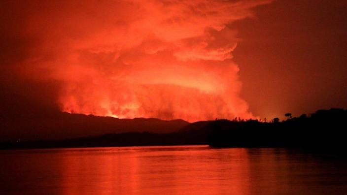 Smoke and flames are seen at the Nyiragongo volcanic eruption from the Tchegera Island on Lake Kivu, near Goma