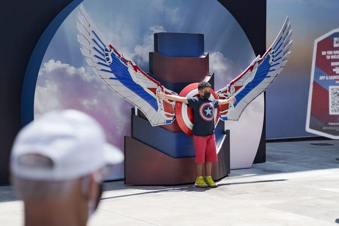 A Disney California Adventure guests poses in front of Captain America's Falcon wings inside the park.