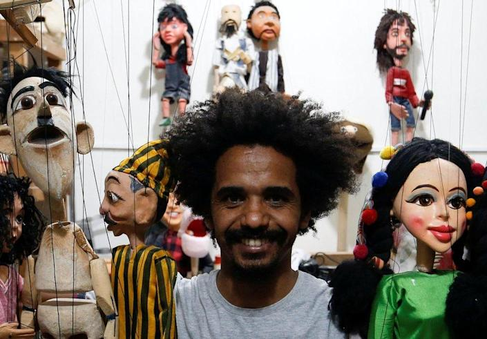 A puppeteer holds his dolls.