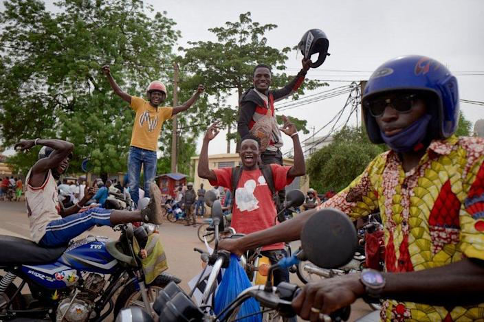 Men pose on top of motorbikes as they celebrate.