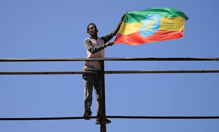 A man standing in an elevated position flies the Ethiopian national flag.