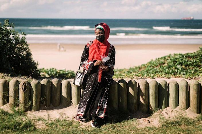 A woman sitting close to the beach clutches a rose.