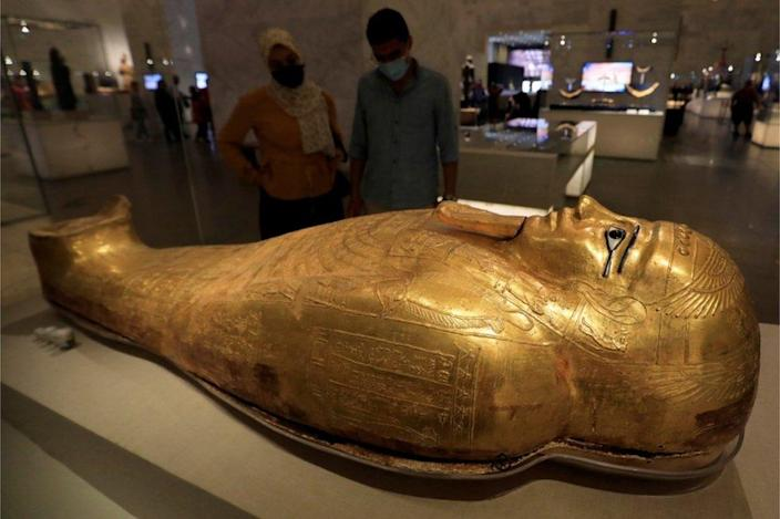 People look at a large gilded sarcophagus.