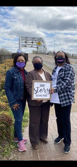 Cheryl Gardner-Davis, left; Elizabeth Steele-Davis, middle; and Mary Hall-Mcguire, right, stand in front of the Edmund Pettus Bridge in Selma, Alabama. The photo shows the members of the three families that housed people on their campsites as they marched from Selma to Montgomery in 1965.