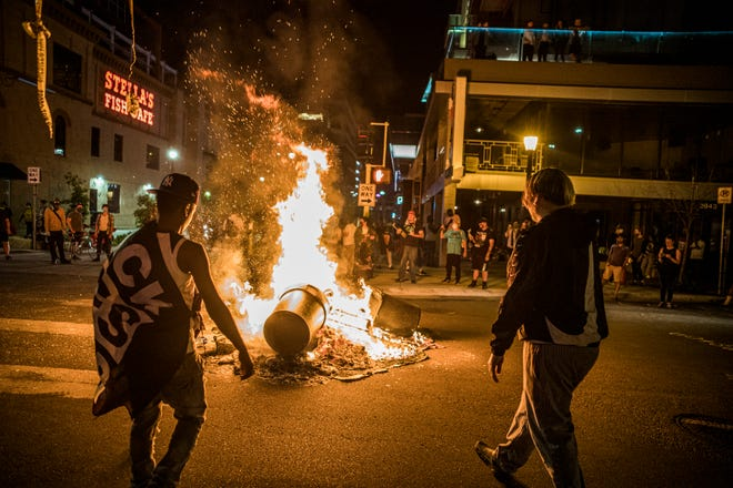 Protesters set a dumpster on fire after a shooting on Thursday, June 3, 2021 in Minneapolis. Crowds vandalized buildings and stole from businesses in Minneapolis' Uptown neighborhood after officials said a man was fatally shot by authorities.