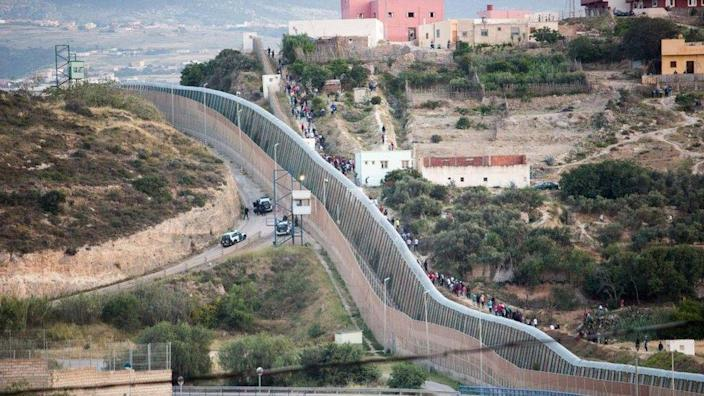 Several people try to reach Spanish soil from the border that separates Melilla and Morocco, 21 May 2021, in Morocco.