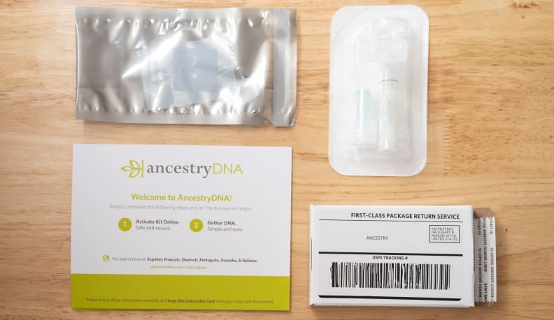 The contents of an AncestryDNA test kit, which features a spit tube, return package, and activation information.