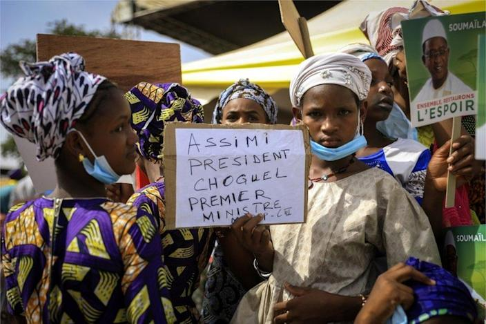 """Demonstrators hold a sign saying """" Assimi president, Choguel prime minister""""."""