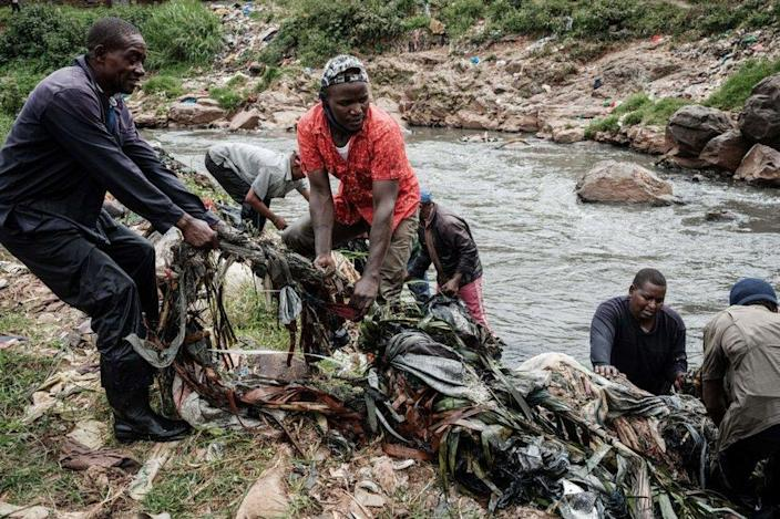 A group of volunteers haul rubbish and debris from a river.