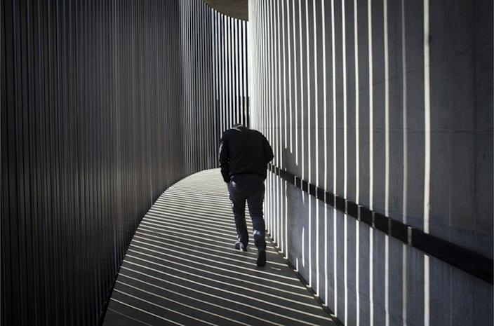 A man walks through shafts of light and shadow.