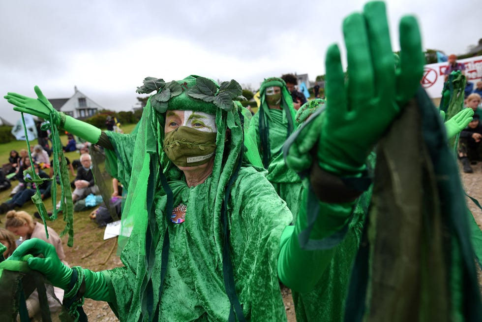 """Activists from the climate change protest group Extinction Rebellion, dressed in green robes and known as """"Green Spirits"""" demonstrate in St Ives, Cornwall on June 11, 2021."""