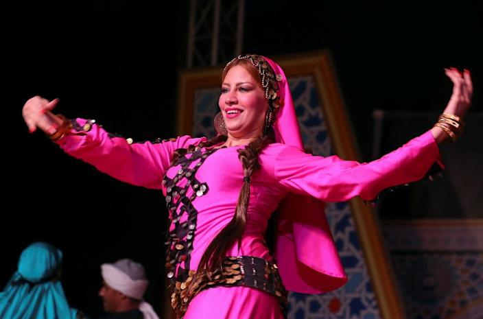 A dancer of the Reda Folkloric Troupe with her hands spread