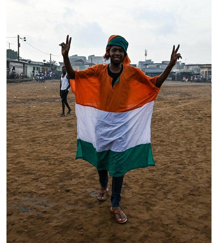 A man in an Ivorian flag making a V for victory sign