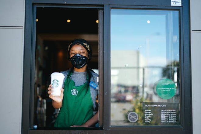 A Starbucks employee hands a cup out through a drive-up window at a Starbucks restaurant.