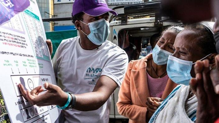 This picture taken in Addis Ababa on June 17, 2021 shows staff members of the National Electoral Board explaining to people how to vote for the upcoming June 21, 2021 elections