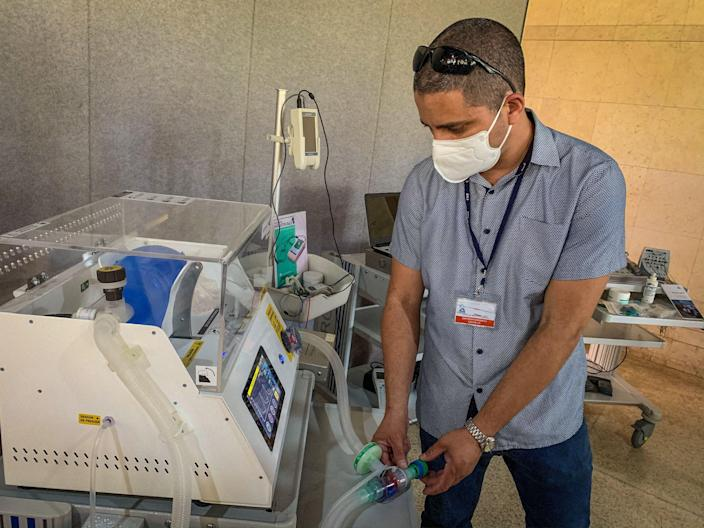 A medical equipment specialist verifies the operation of an artificial respiration device built by the Cuban medical technology manufacturer ComBiomed, in Havana, March 31, 2021. Cuba opted to build much of its own technological arsenal to deal with COVID-19 due to the U.S. embargo and the lack of foreign currency in the country. / Credit: ADALBERTO ROQUE/AFP/Getty
