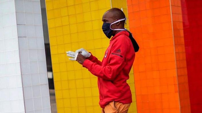 A man wearing a face mask puts on a pair of gloves at the entrance of a shopping mall in Alexandra, Johannesburg, in 2020.