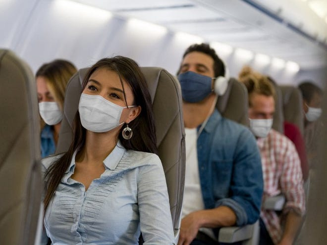 A row of masked passengers on an airplane.