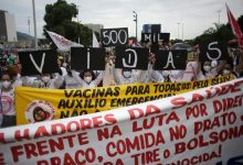 """Women simultaneously hold up placards with a message that reads in Portuguese; """"500K deaths! His fault!"""" during a demonstration against Brazilian President Jair Bolsonaro's handling of the coronavirus pandemic and economic policies protesters say harm the interests of the poor and working class, in Rio de Janeiro, Brazil, Saturday, June 19, 2021."""