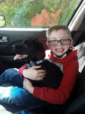 Bryson Kliemann sits with his dog, Bruce. When Bruce got sick, Bryson decided to sell his prized Pokémon cards to save his dog's life.