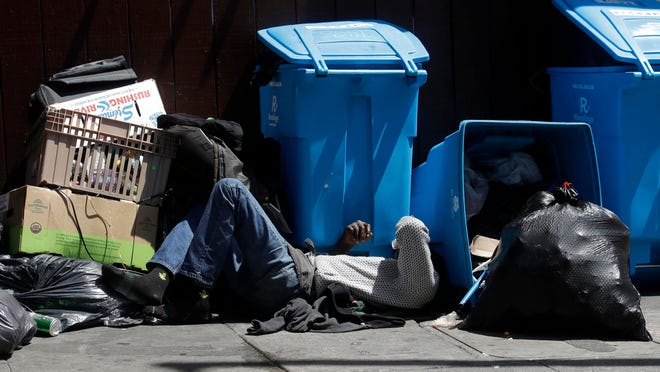 A homeless man sleeps in front of recycling bins and garbage on a street corner in San Francisco.