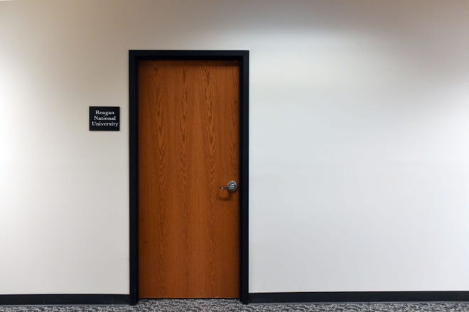 A sign for Reagan National University is posted outside one of two locked doors in a Sioux Falls office building in January 2020.