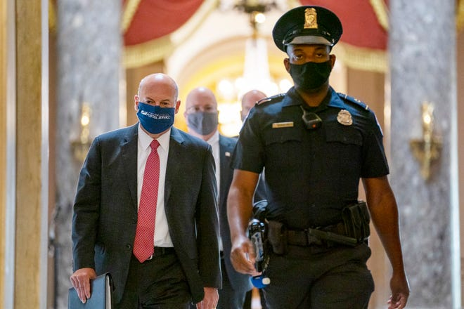 Postmaster General Louis DeJoy, left, is escorted to House Speaker Nancy Pelosi's office on Capitol Hill in Washington on Aug. 5, 2020. Several individuals including candidates for public office sued President Donald Trump and the U.S. Postal Service's new postmaster general in New York on Aug. 17, 2020 to ensure adequate funding for postal operations. The lawsuit was filed in Manhattan federal court as multiple lawsuits were threatened across the country as a response to comments the president recently made and actions taken by DeJoy to change operations at post offices nationwide.